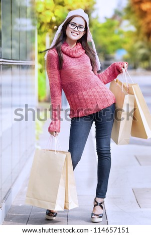 Portrait of friendly girl carrying shopping bag and dressed for winter time with hat on her head.