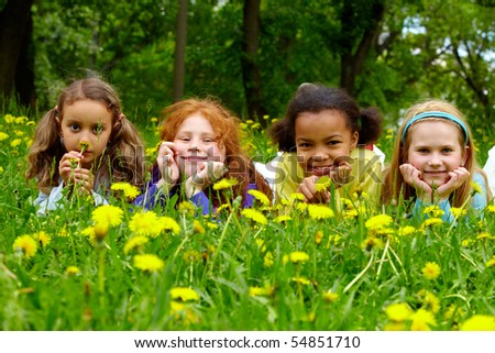 Portrait of friendly girls relaxing in park on summer day - stock photo