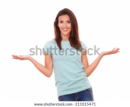 Portrait of friendly hispanic woman holding her palms up while standing and smiling at you on isolated white background - copyspace
