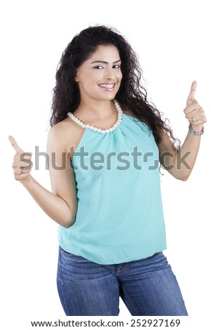Portrait of friendly indian woman with curly hair showing thumb up in the studio, isolated on white - stock photo