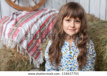 Portrait of friendly little blond girl villager in wooden hayloft with vintage decoration - stock photo