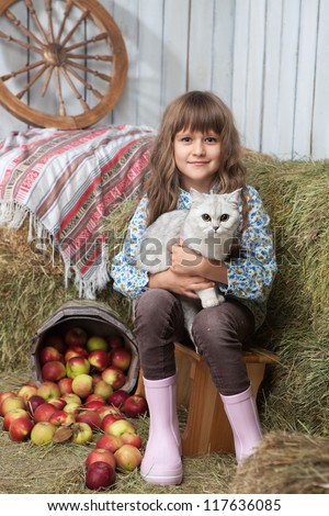 Portrait of friendly little blond girl villager sitting with white cat on hands near stacks of hay, pail of apples in wooden hayloft - stock photo