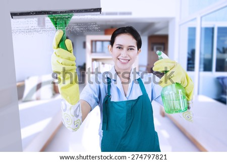 Portrait of friendly maid wearing uniform and apron, cleaning a mirror with a spray while smiling - stock photo