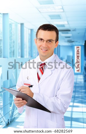 Portrait of friendly medical doctor in hospital  with medical pad. - stock photo