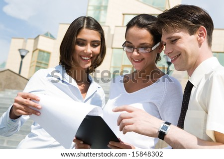 Portrait of friendly people discussing new business plan outdoors during meeting - stock photo