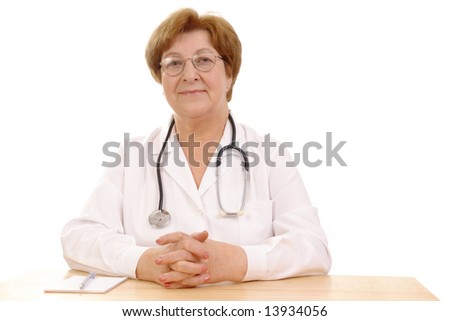 Portrait of friendly senior family doctor with stethoscope sitting behind a desk over white background