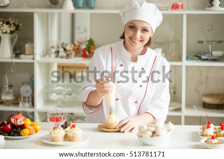 Portrait of friendly smiling female professional confectioner topping a cupcake with cream using a pastry bag. Looking at the camera. Indoors image. Pastry chef woman making creamy cakes