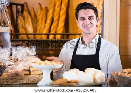 Portrait of friendly smiling male baker at bakery display with pastry and bread - stock photo