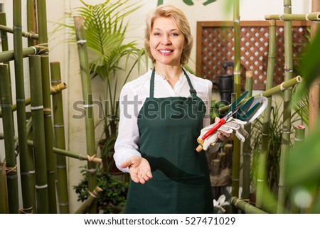 Portrait of friendly smiling mature woman florist with tools in hands among green plants in floral shop