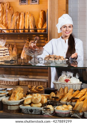 Portrait of friendly smiling young woman at bakery display with pastry - stock photo