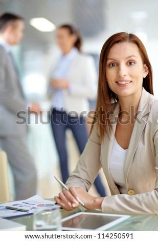 Portrait of friendly specialist looking at camera on the background of working colleagues - stock photo