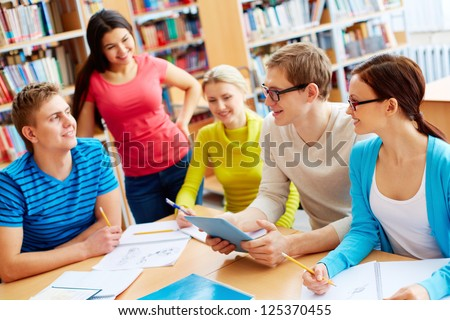 Portrait of friendly students sitting in college library and doing homework - stock photo