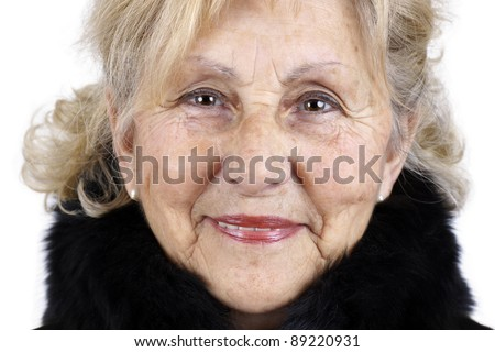 Portrait of friendly sympathetic senior woman smiling looking at camera with black fur collar; great details showing all signs of aging. - stock photo