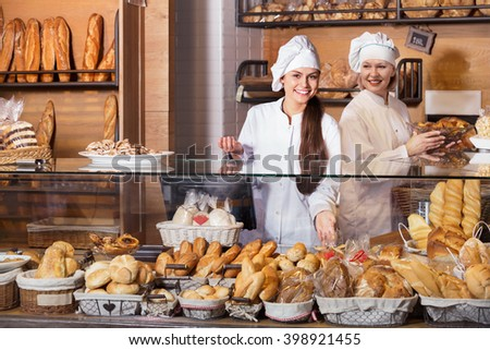 Portrait of friendly women at bakery display with pastry - stock photo