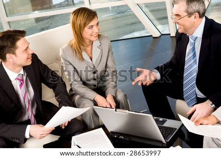 Portrait of friendly workteam communicating with each other in office at meeting - stock photo
