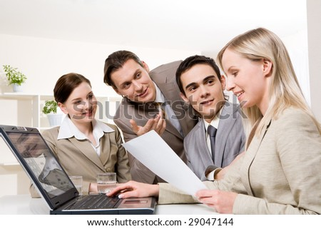 Portrait of friendly workteam looking at confident businesswoman with document in hand and sharing their ideas