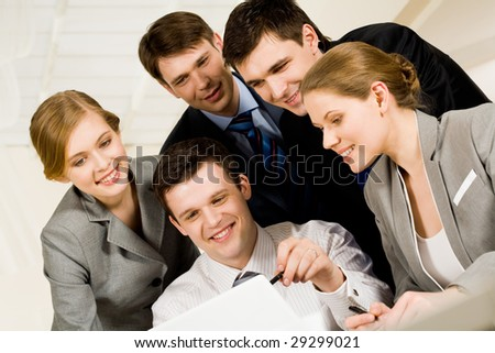 Portrait of friendly workteam looking at monitor of laptop while confident businessman pointing at screen