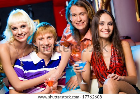 Portrait of friendly young people looking at camera with smiles in the bar