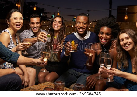 Portrait Of Friends Enjoying Night Out At Rooftop Bar