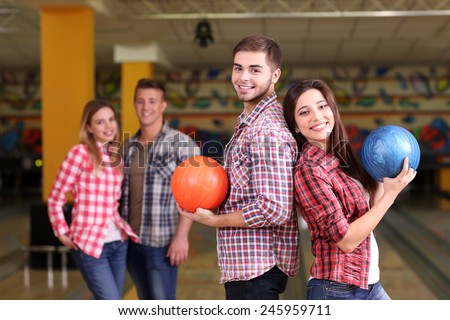 Portrait of friends in bowling club - stock photo