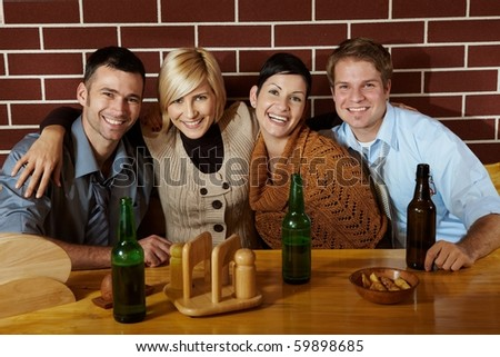 Portrait of friends in pub, sitting at table, smiling at camera.? - stock photo