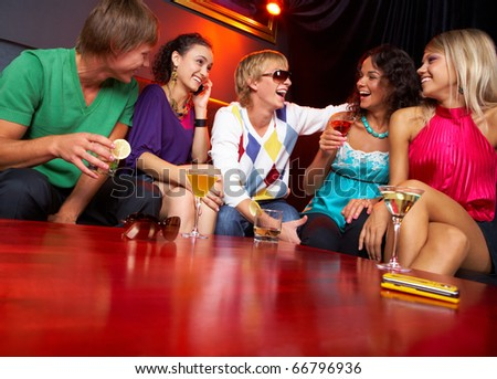 Portrait of friends sitting on the sofa and chatting in the nightclub - stock photo