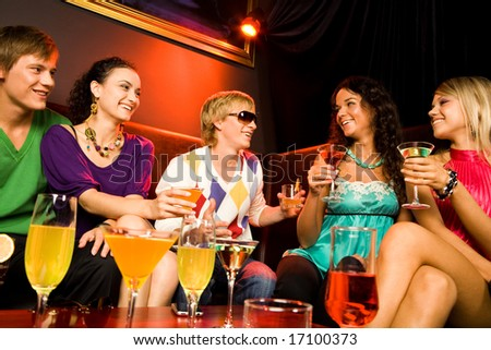 Portrait of friends sitting on the sofa and holding the cocktails in the nightclub - stock photo