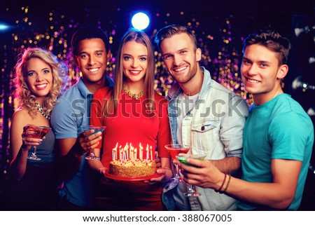 Portrait of friends with birthday cake enjoying the party