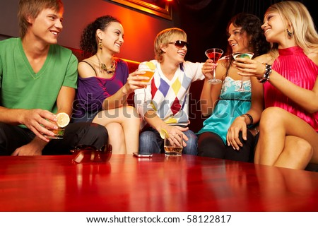 Portrait of friends with cocktails sitting on the sofa in the nightclub and chatting