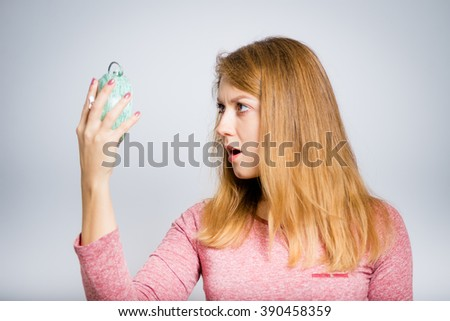 Portrait of frightened young woman looks at an alarm clock, isolated on a gray background - stock photo
