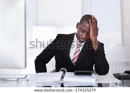 Portrait Of Frustrated African Businessman With Bills And Calculator - stock photo