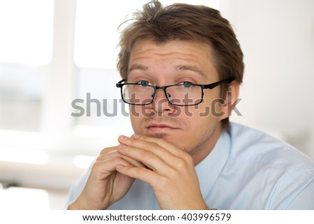 Portrait of frustrated business man wearing glasses. Businessman sitting at his office not knowing what to do. Apathy, crisis, indifference and depression concept.