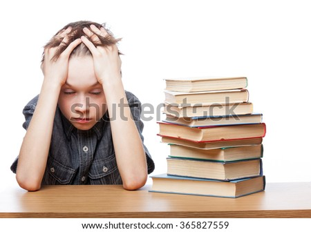 Portrait of frustrated schoolboy sitting at a desk with books holding his head having learning problems - stock photo