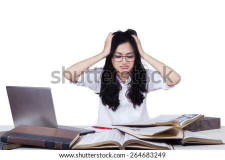 Portrait of frustrated teenage girl reading many literature to prepare her exam
