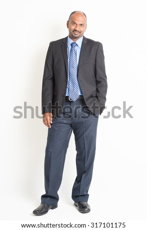 Portrait of full body mature Indian business man arms crossed, standing on plain background. - stock photo