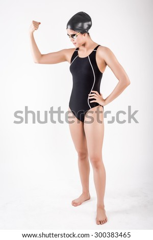 portrait of full body young female swimmer in blue swimsuit with goggle and swimming hat. strong posing in studio set white background - stock photo
