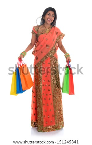 Portrait of full length beautiful traditional Indian woman in sari dress holding shopping bags, isolated over white background.  - stock photo