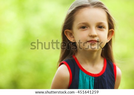 Portrait of funny and sweet little girl outdoors with curly hair in the wind. Close up. Copy-space - stock photo