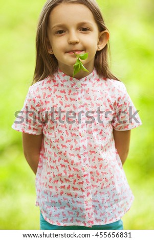Portrait of funny and sweet little girl with long light brown hair. Trendy casual look. Leaves in mouth. Close up. Outdoor shot - stock photo