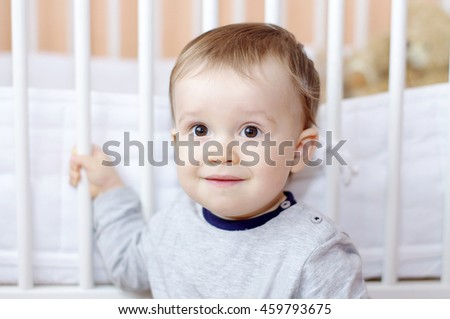 portrait of funny baby age of 1 year against white bed