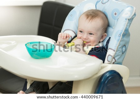 Portrait of funny baby boy sitting in highchair and playing with spoon and dish