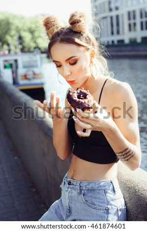 Portrait of funny beautiful girl eating donut. Hungry woman licking fingers