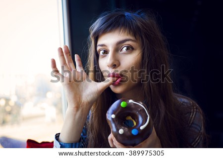 Portrait of funny beautiful girl eating donut with coffee. Hungry woman licking fingers in the cafe and having fun. Cute hipster. Big eyes. LOL  - stock photo