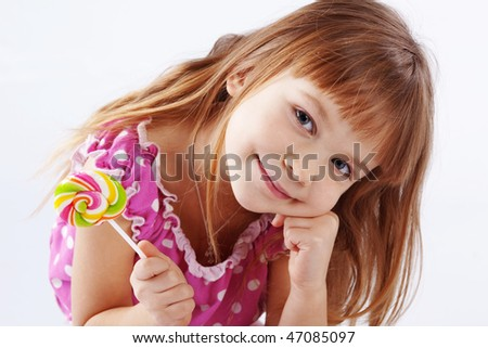 Portrait of funny child eating sweet candy