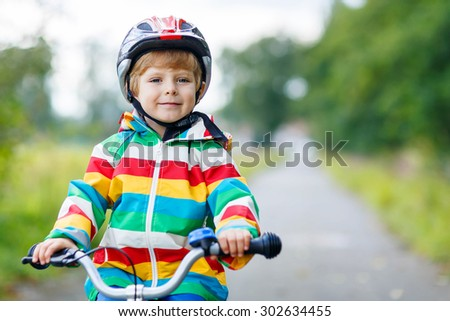 Portrait of funny cute kid with helmet on bicycle on summer day. Active leisure for children outdoors.