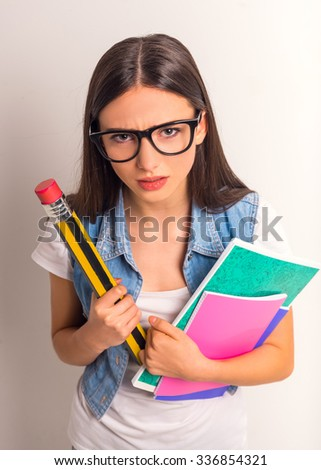 Portrait of funny girl teenager with pencil and notebooks on a white background - stock photo