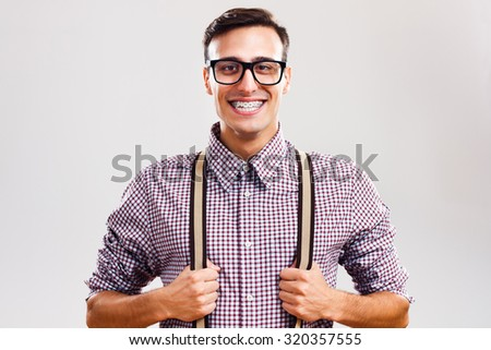 Portrait of funny handsome nerd guy pulling his suspenders.I am so handsome! - stock photo
