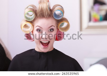 Portrait of funny happy woman in beauty salon. Cheerful blond girl with hair curlers rollers by hairdresser. Hairstyle. - stock photo