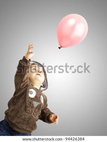 portrait of funny kid trying to hold a pink balloon over grey background - stock photo