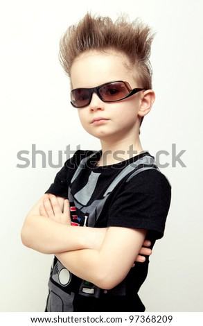 portrait of funny kid wearing sunglasses against a white background